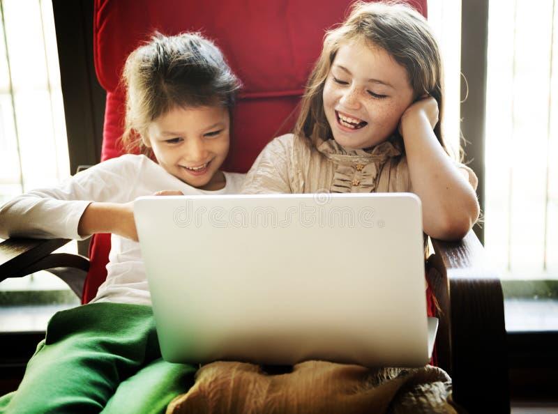 Niñas que juegan con un ordenador portátil fotografía de archivo libre de regalías