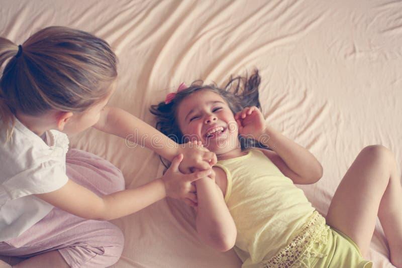 Niñas que juegan junto en cama foto de archivo libre de regalías