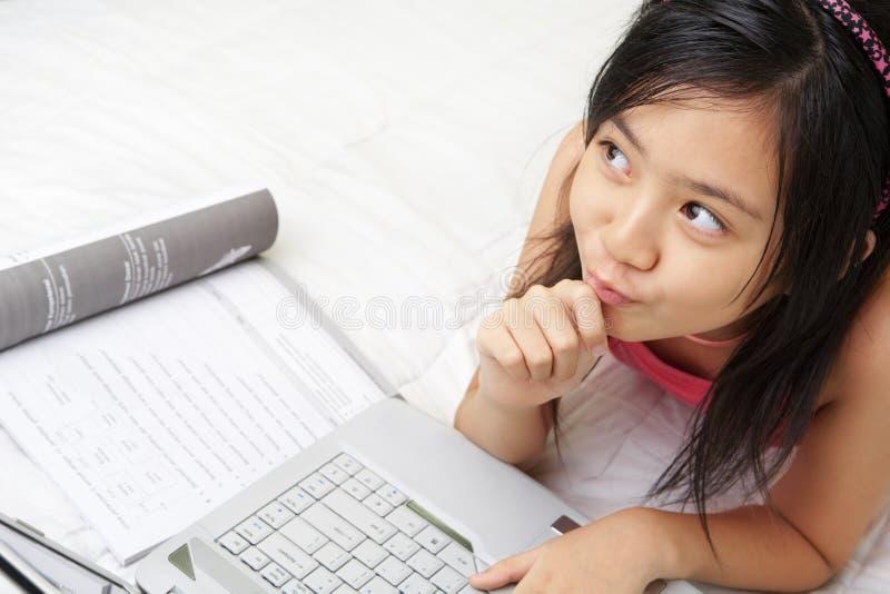 Niñas que juegan la computadora portátil mientras que estudia fotos de archivo libres de regalías