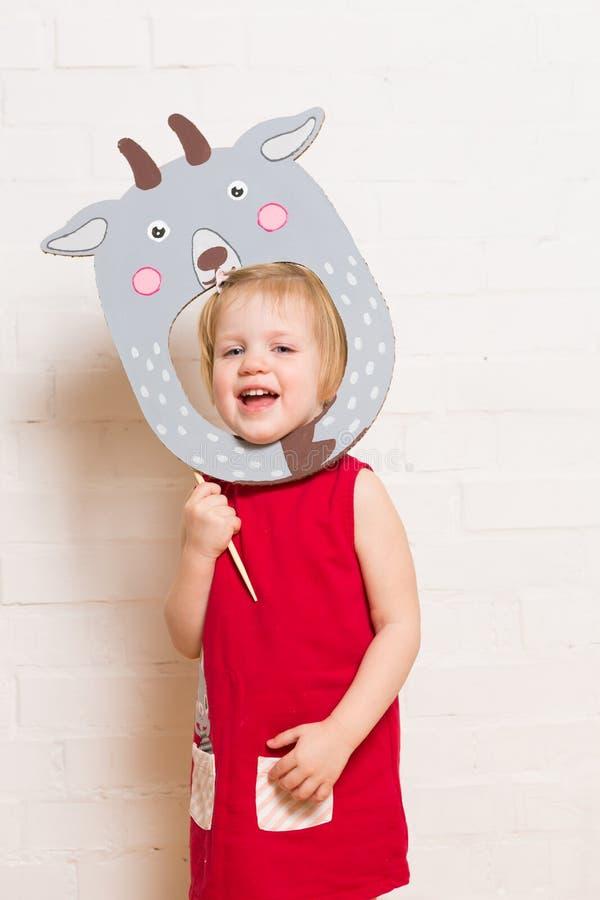 Niñas que llevan a cabo la máscara de la cabra en el fondo blanco imagen de archivo libre de regalías