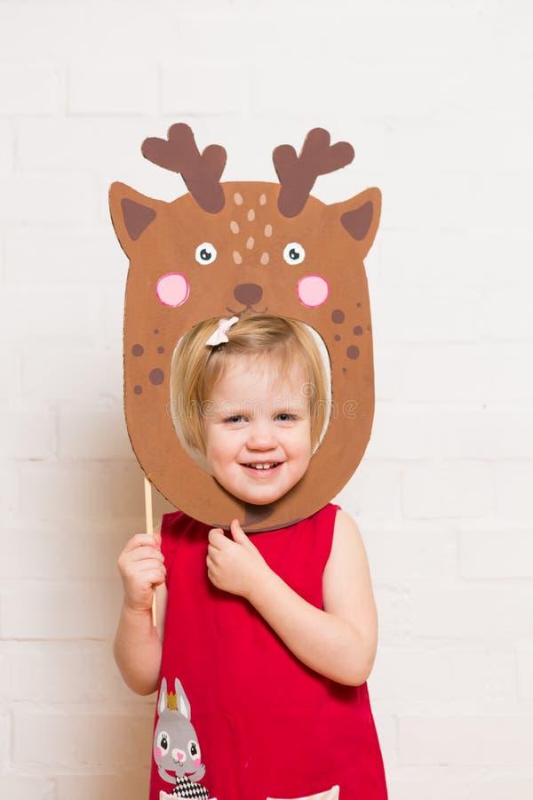 Niñas que llevan a cabo la máscara de los ciervos en el fondo blanco foto de archivo