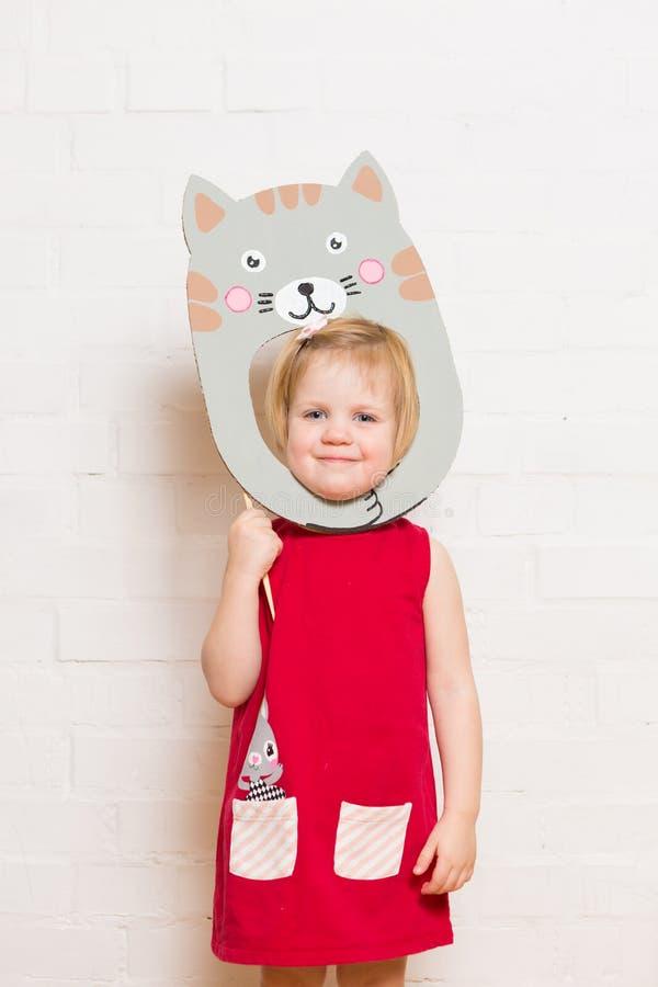 Niñas que llevan a cabo la máscara del gato en el fondo blanco foto de archivo libre de regalías