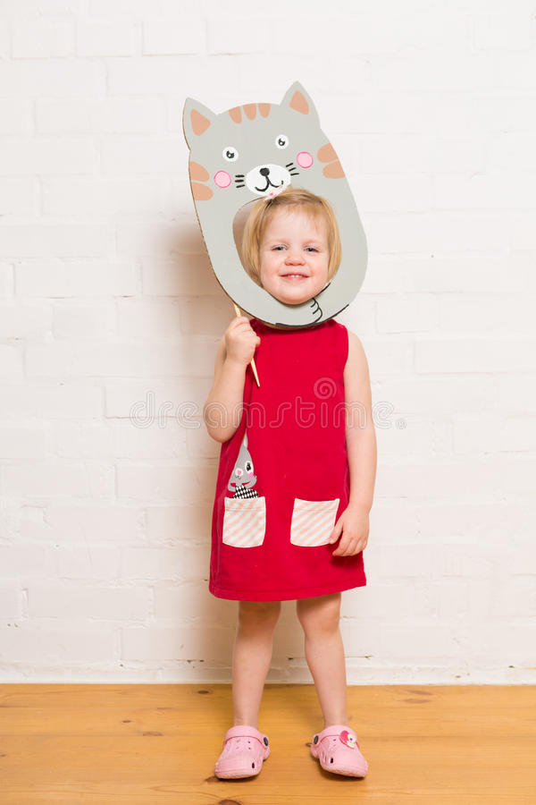 Niñas que llevan a cabo la máscara del gato en el fondo blanco fotos de archivo libres de regalías