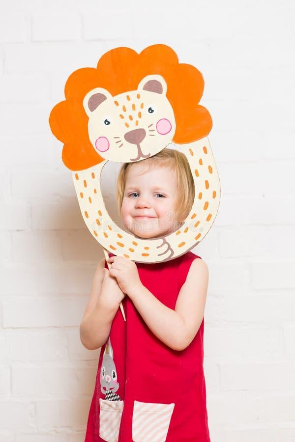 Niñas que llevan a cabo la máscara del león en el fondo blanco foto de archivo libre de regalías