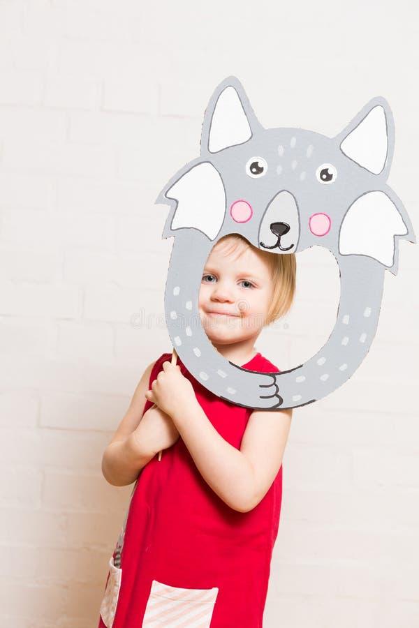 Niñas que llevan a cabo la máscara del lobo en el fondo blanco fotos de archivo