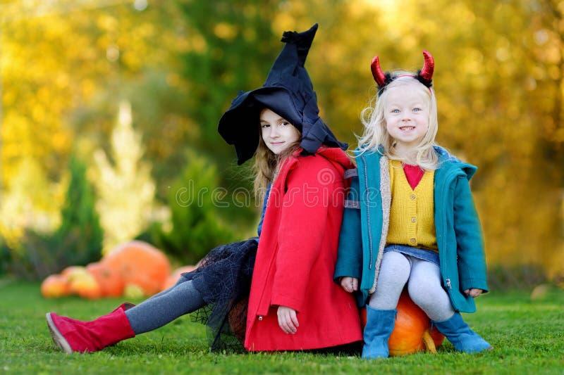 Niñas que llevan el traje de Halloween en un remiendo de la calabaza imagenes de archivo