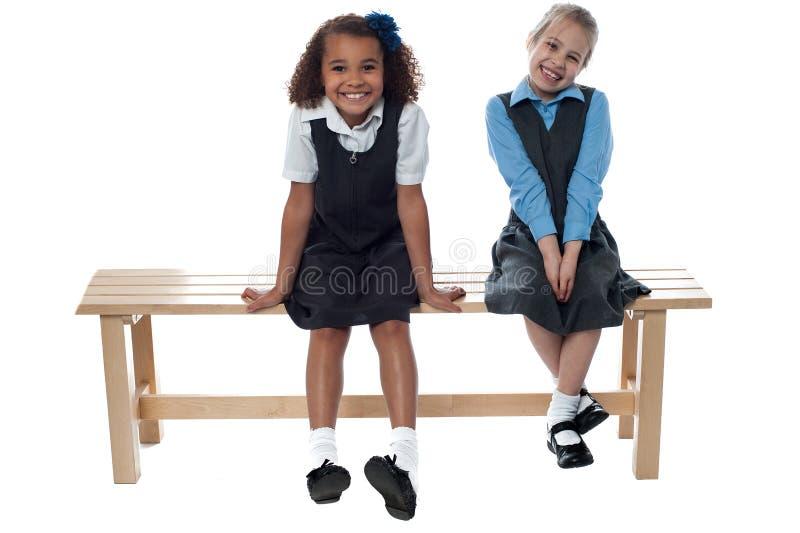 Niñas que se sientan en el banco foto de archivo