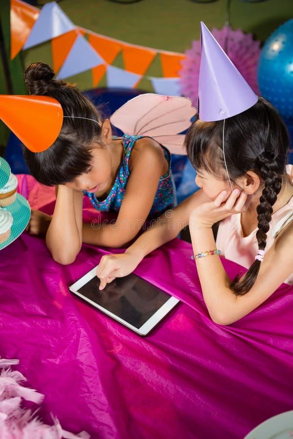 Niñas que usan la tableta en el partido imagenes de archivo