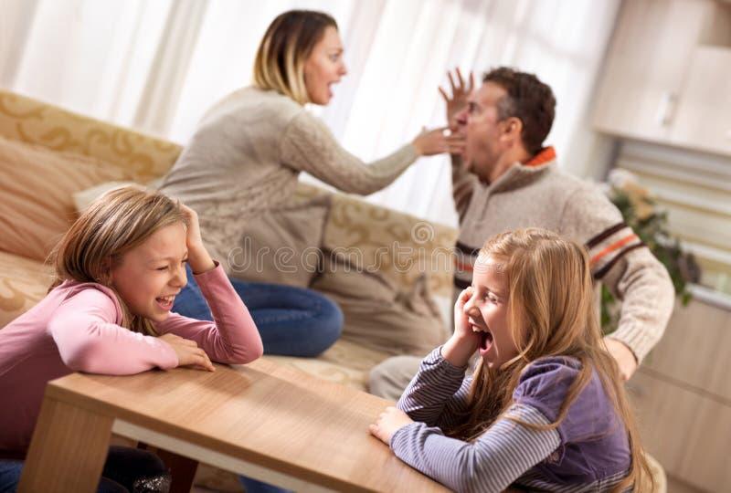Niñas tristes que gritan mientras que sus padres están discutiendo en fotografía de archivo libre de regalías