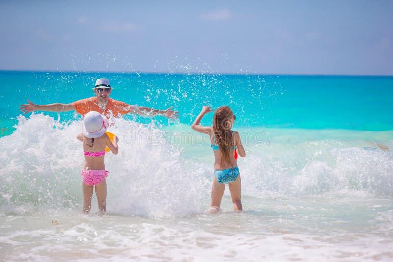 Niñas y papá feliz que se divierten en la natación y el funcionamiento de la costa imágenes de archivo libres de regalías