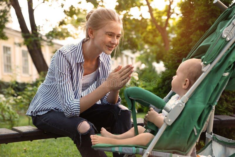 Niñera adolescente con bebé en un coche de paseo jugando en el parque imágenes de archivo libres de regalías