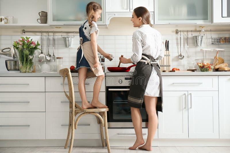 Niñera joven con la niña linda que cocina junto foto de archivo