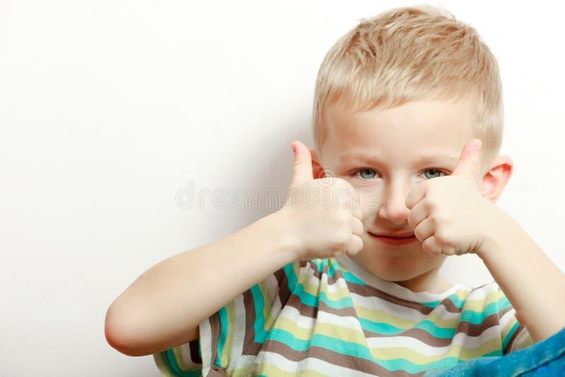 Niñez feliz El niño rubio sonriente del muchacho embroma mostrar el pulgar para arriba fotos de archivo