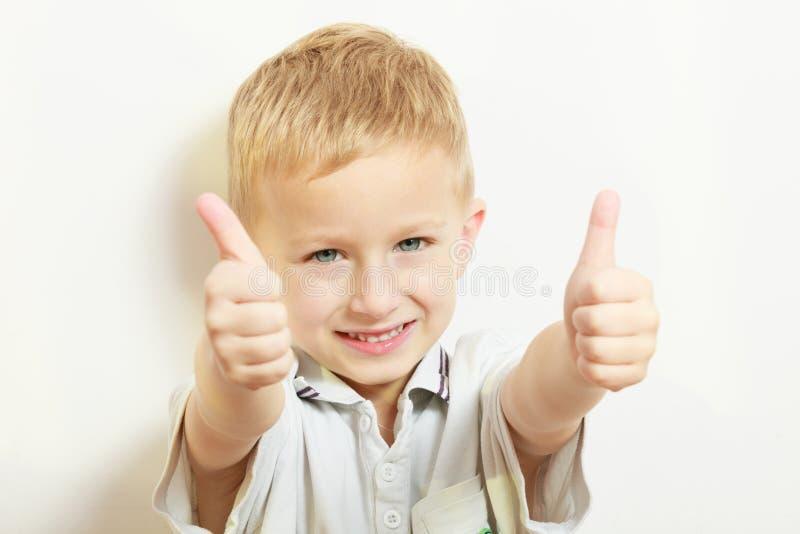 Niñez feliz El niño rubio sonriente del muchacho embroma mostrar el pulgar para arriba fotos de archivo libres de regalías