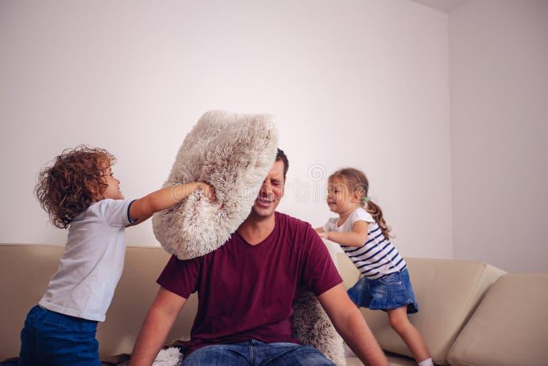 Niñez feliz - niños muchacho y muchacha que juegan con el toge del padre imagenes de archivo
