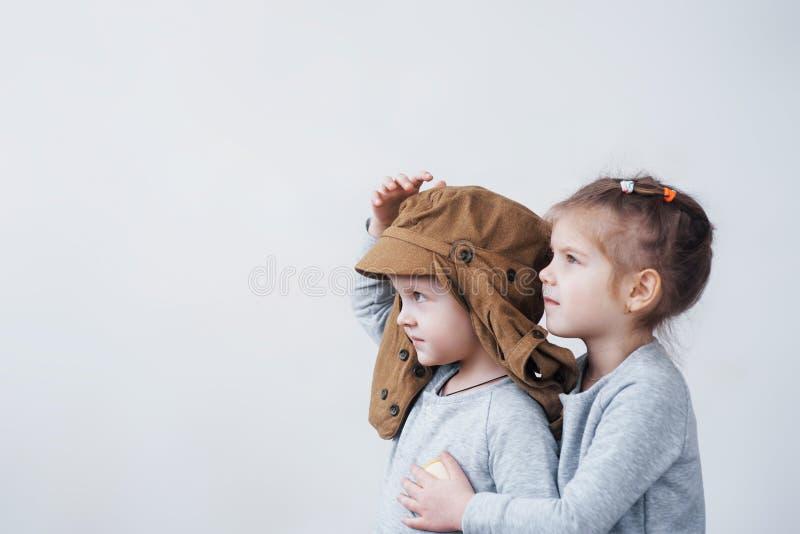 Niñez juguetona Niño pequeño que se divierte con la caja de cartón Muchacho que finge ser piloto Niño pequeño y muchacha que se d foto de archivo libre de regalías