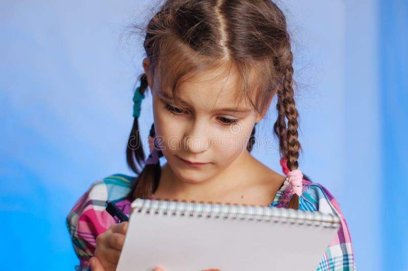 niñita se para y escribe en un cuaderno foto de archivo