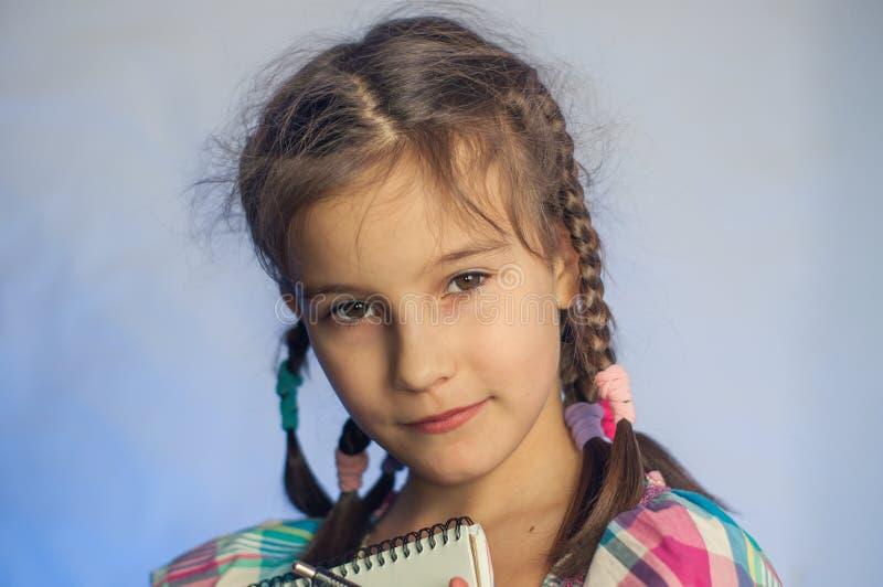 niñita se para y escribe en un cuaderno imagen de archivo