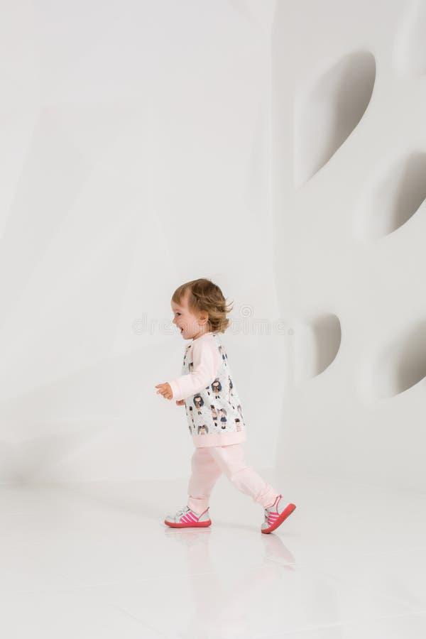 Niño año que se coloca cerca de la pared blanca en estudio fotos de archivo libres de regalías