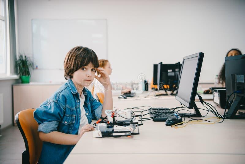 niño adolescente que mira la cámara mientras que programa el robot diy imagenes de archivo