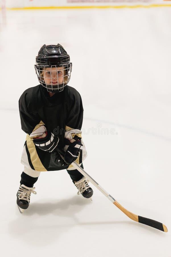 Niño adorable 3 años del hockey de los juegos en el hielo que lleva en el equipo lleno del hockey fotos de archivo libres de regalías