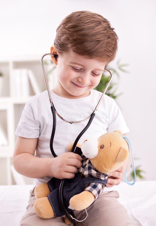 Niño adorable con el estetoscopio del oso de peluche de examen del doctor imagen de archivo