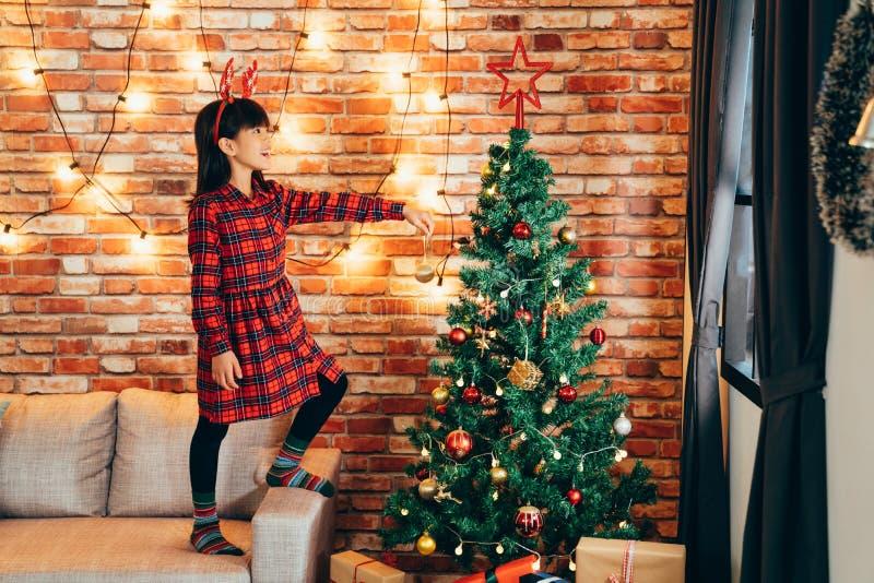 Niño adorable de la muchacha que adorna el árbol de navidad fotografía de archivo