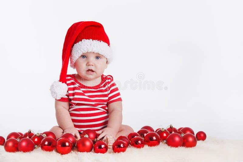 Niño adorable en el casquillo de santa con las pilas de actuales cajas alrededor de sentarse en el piso. Aislado en el fondo blanc foto de archivo