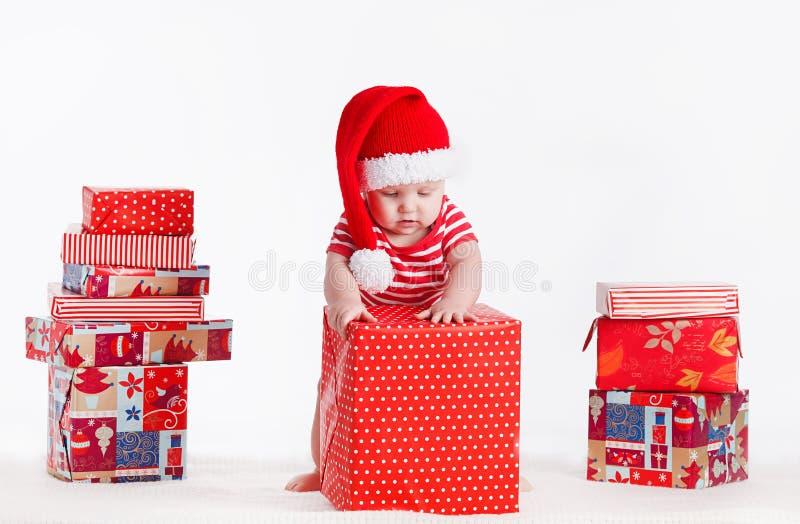Niño adorable en el casquillo de santa con las pilas de actuales cajas alrededor de sentarse en el piso. Aislado en el fondo blanc fotos de archivo