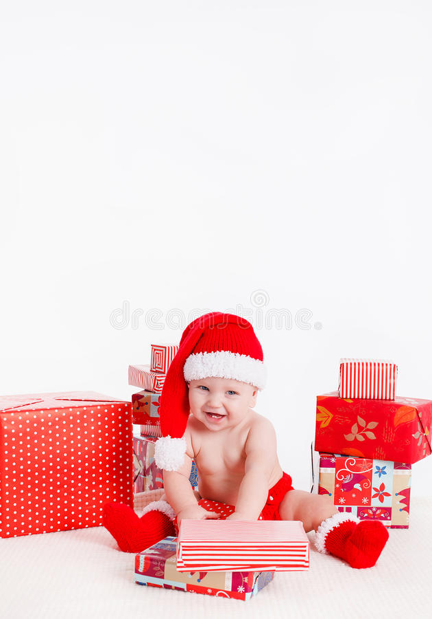 Niño adorable en el casquillo de santa con las pilas de actuales cajas alrededor de sentarse en el piso. Aislado en el fondo blanc imagen de archivo