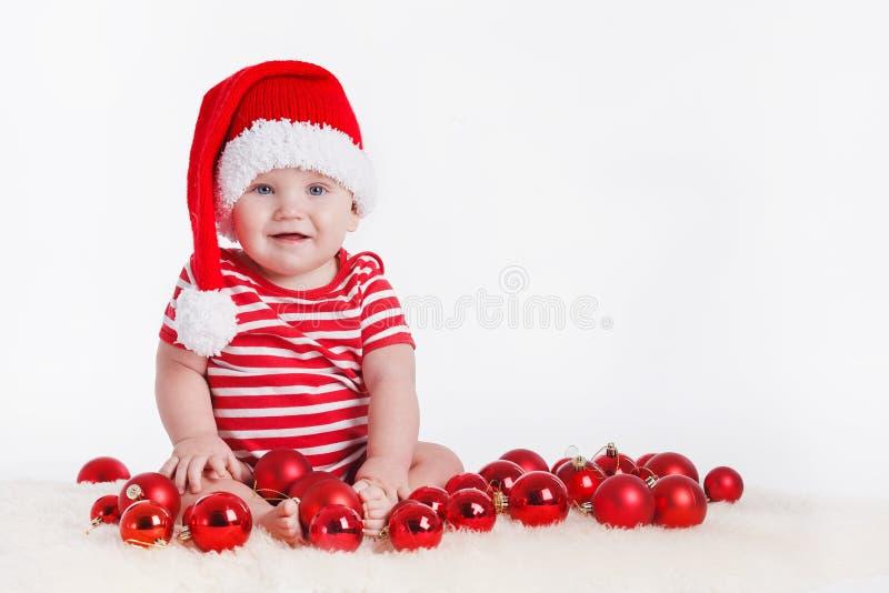 Niño adorable en el casquillo de santa con las pilas de actuales cajas alrededor de sentarse en el piso. Aislado en el fondo blanc imágenes de archivo libres de regalías
