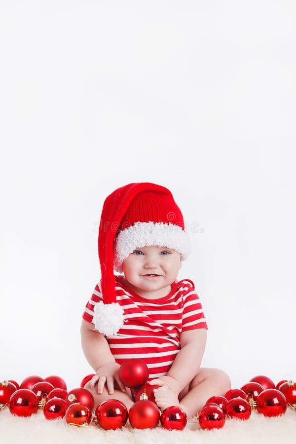 Niño adorable en el casquillo de santa con las pilas de actuales cajas alrededor de sentarse en el piso. Aislado en el fondo blanc fotografía de archivo
