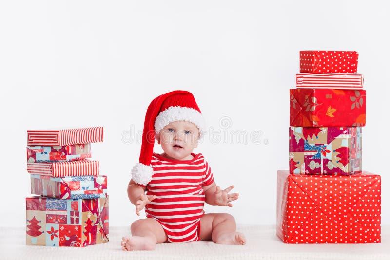Niño adorable en el casquillo de santa con las pilas de actuales cajas alrededor de sentarse en el piso. Aislado en el fondo blanc fotos de archivo libres de regalías