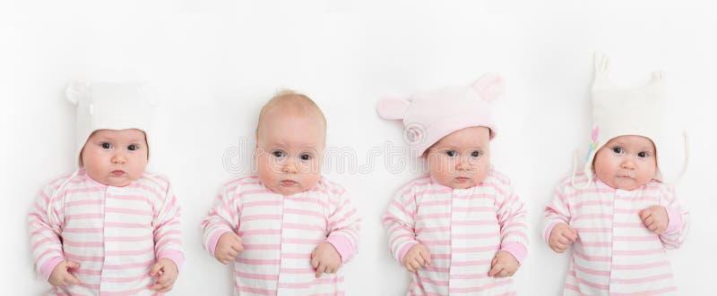 Niño adorable lindo del bebé con diversos sombreros blancos y rosados calientes Bebé feliz en el fondo blanco y mirada fotos de archivo libres de regalías