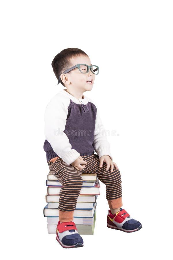 Niño adorable que estudia con los libros y los vidrios que llevan fotos de archivo