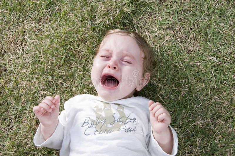 Niño adorable que grita y que miente en el jardín imagen de archivo