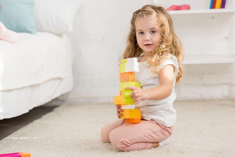 niño adorable que juega con el constructor plástico coloreado en la alfombra en sitio y la mirada de niños fotografía de archivo libre de regalías