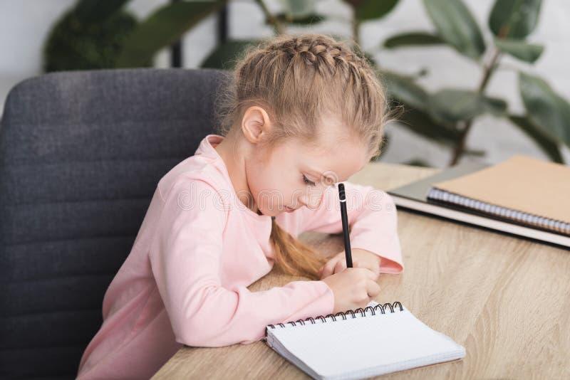 niño adorable que se sienta en el escritorio y estudiar imagenes de archivo