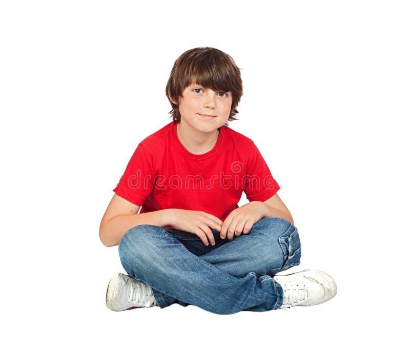 Niño adorable que se sienta en el suelo fotografía de archivo