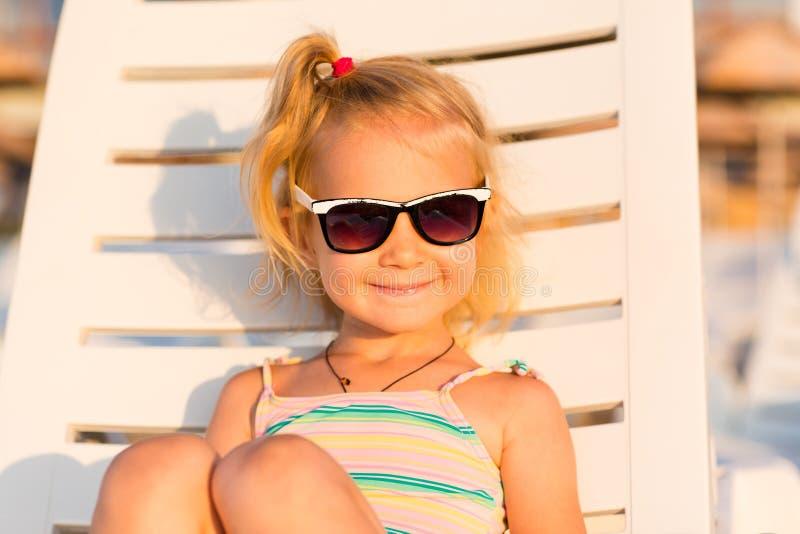Niño adorable que toma el sol en una playa fotos de archivo libres de regalías