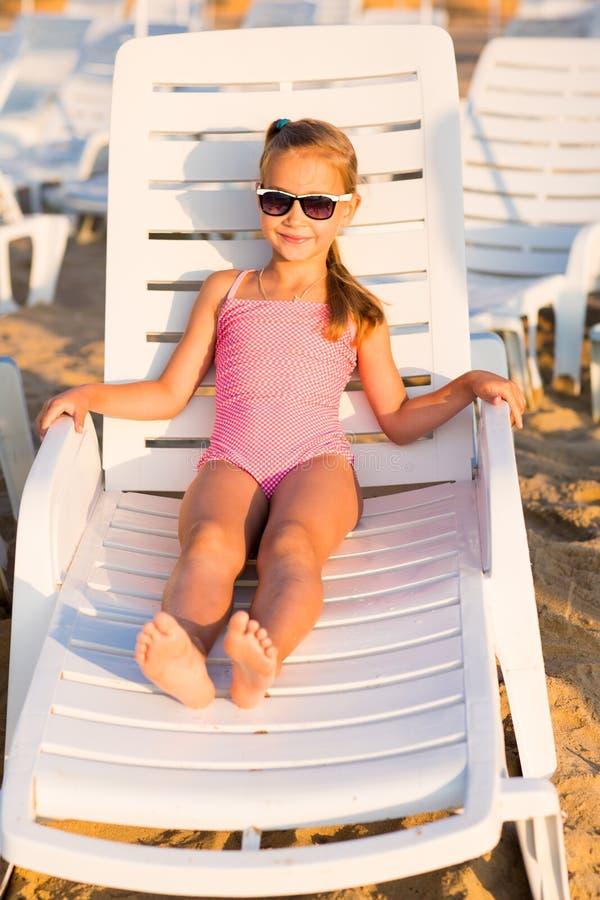 Niño adorable que toma el sol en una playa fotografía de archivo
