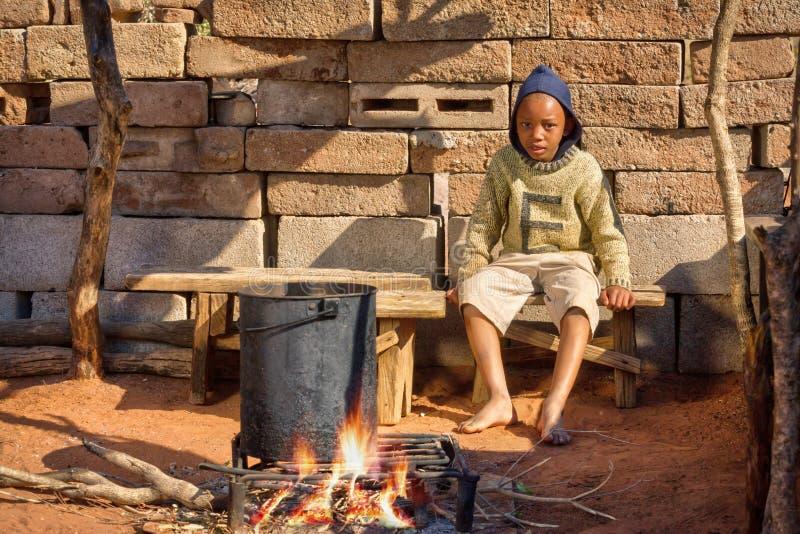 Niño africano que cocina en la cocina del verano fotografía de archivo