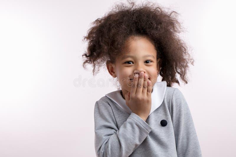Niño afro que ríe nerviosamente con el ponitail divertido que mira la cámara imagenes de archivo