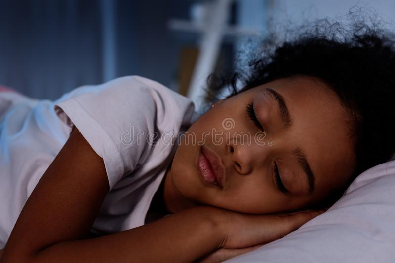 niño afroamericano adorable que duerme en cama fotografía de archivo