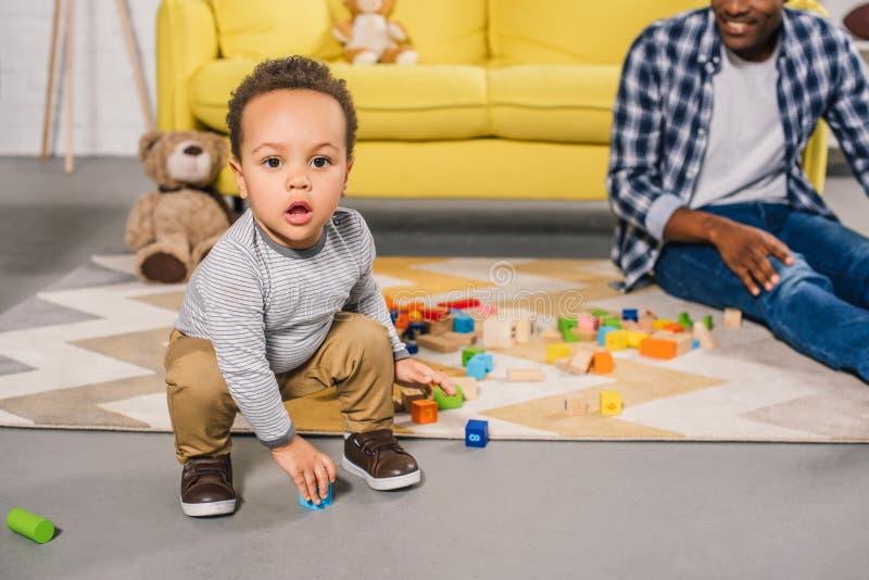 niño afroamericano adorable que mira la cámara mientras que juega con el padre fotografía de archivo