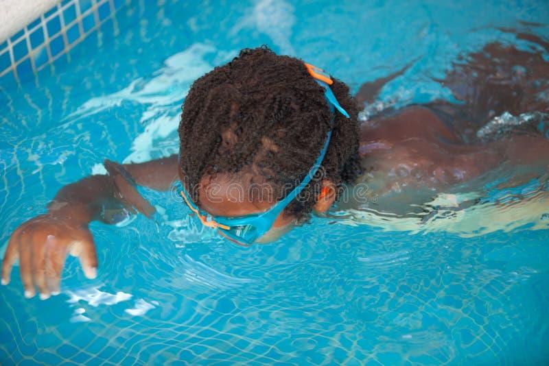 Niño afroamericano con las gafas en la piscina imágenes de archivo libres de regalías