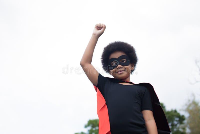 Niño afroamericano del superhéroe en postura del lanzamiento - con el espacio de la copia imagen de archivo