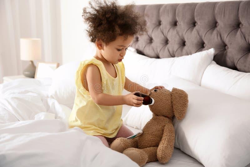 Niño afroamericano lindo que se imagina como doctor mientras que juega con el conejito del juguete imagen de archivo libre de regalías