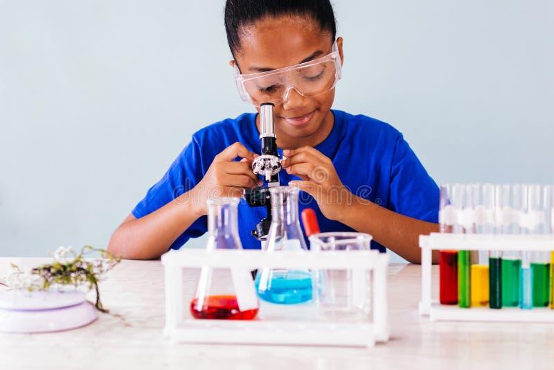 Niño afroamericano que mira en el microscopio en laboratorio imágenes de archivo libres de regalías