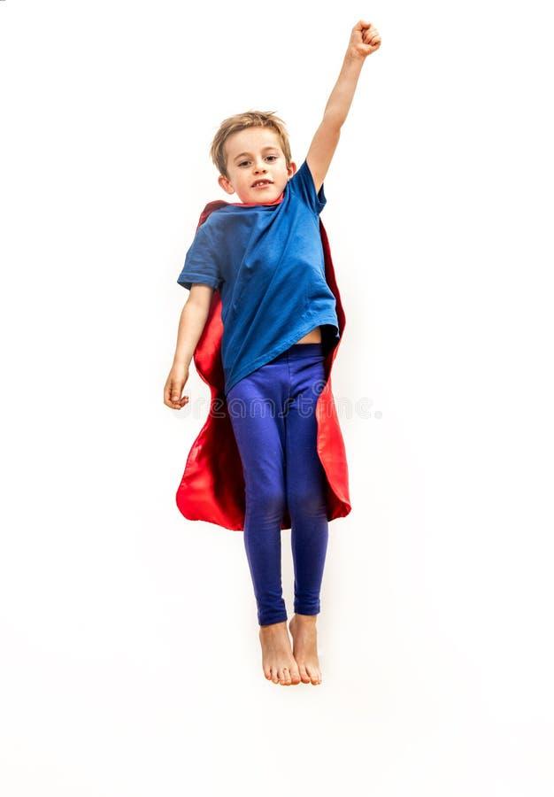 Niño aislado que alcanza arriba como el super héroe potente, fingiendo alcanzando algo imagen de archivo libre de regalías